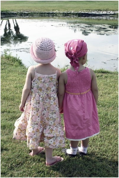 adelaine-and-peyton-two-cancer-girls-sitting-by-the-lake-holding-hands-2-may-13-2007